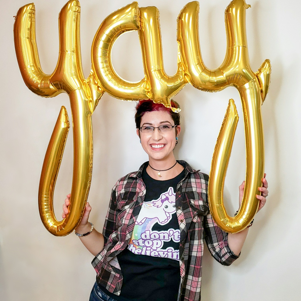 "woman with holding a balloon that says ""yay"""