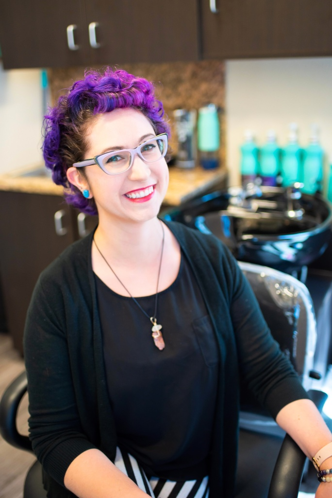 woman with purple hair and purple glasses smiling in a hair salon